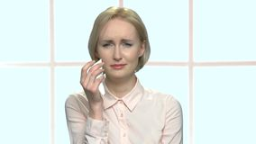 Beautiful blonde office woman is crying. Front view crying female office worker on checkered window background. Personal toubles concept stock video