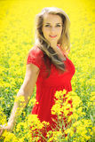 Beautiful blonde in oilseed Rape. Beautiful blonde in red dress posing in oilseed Rape, fashion photography Stock Photography