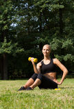 The beautiful blonde in park with dumbbells Royalty Free Stock Photography
