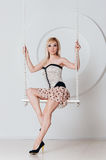 Beautiful blonde with a perfect figure on swing Royalty Free Stock Photography