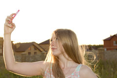 Beautiful blonde photographs on the phone Royalty Free Stock Images