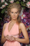 Beautiful blonde in a pink dress in the garden Royalty Free Stock Photo