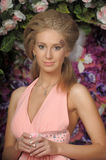 Beautiful blonde in a pink dress in the garden Stock Photos
