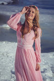 Beautiful blonde in a pink dress outdoors in winter royalty free stock image