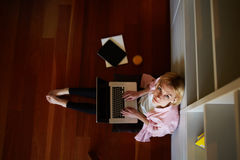 Beautiful blonde in pink shirt sitting on the floor with a computer on his lap. Top view young female freelancer busy working on laptop computer while leaning on Stock Image