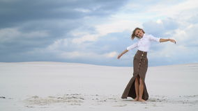 Beautiful blonde posing in the middle of the desert against a background of clouds stock footage