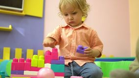 Beautiful blonde preschool cute toddler playing with multi coloured building blocks in kindergarten. Child development