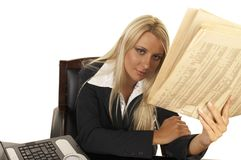 Beautiful Blonde Reading Newspaper. Young businesswoman reading newspaper royalty free stock photos