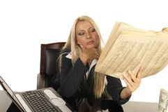 Beautiful Blonde Reading Newspaper. Young businesswoman reading newspaper stock photos