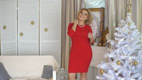 Beautiful blonde in red dress posing for the camera stock footage