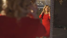 Beautiful blonde in red dress posing in the mirror stock video footage