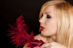 Beautiful blonde with a red feather Stock Images