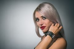 Beautiful blonde with red lips on a dark background in a collar. Portrait of a beautiful blonde with red lips on a dark background in a collar with spikes stock photo