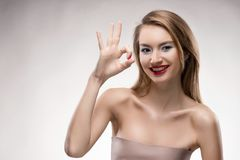 The beautiful blonde red lips smiling girl shows the sign ok. Isolated on a white background. Healthy clean leather. Manicure - red nails. Copy space Stock Photography