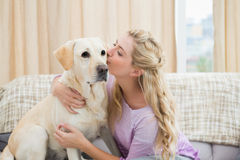 Beautiful blonde relaxing on the couch with pet dog Royalty Free Stock Images