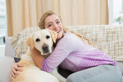 Beautiful blonde relaxing on the couch with pet dog Royalty Free Stock Image