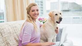 Beautiful blonde relaxing on the couch with pet dog Stock Image