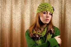 Beautiful blonde in retro cap and scarf. Portrait of a beautiful blonde in retro cap and scarf over shiny curtain background Royalty Free Stock Photography