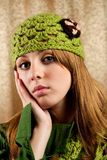 Beautiful blonde in retro cap and scarf. Portrait of a beautiful blonde in retro cap and scarf over shiny curtain background Stock Photography