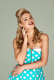 Beautiful blonde retro fashion model in a pink polka dot dress posing in front of a studio background with dots. Beautiful blonde retro fashion model in a blue Stock Image