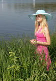 Beautiful blonde on the riverbank. Royalty Free Stock Image