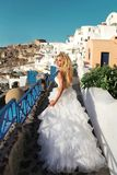 Beautiful blonde runaway bride in white wedding dress on the isl. Beautiful bride, blonde model in amazing wedding dress runs to Santorini in Greece. Fleeing Stock Photography