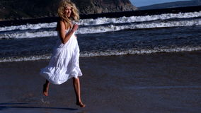 Beautiful blonde running in white dress on sunny day at the beach