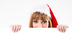 Beautiful blonde in a santa hat looking from behind a blank billboard Royalty Free Stock Images