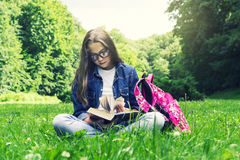 Beautiful blonde schoolgirl girl in jeans shirt reading a book on grass with a backpack in the park Royalty Free Stock Images