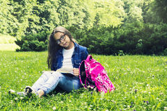 Beautiful blonde schoolgirl girl in jeans shirt reading a book on grass with a backpack in the park Royalty Free Stock Image