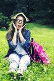 Beautiful blonde schoolgirl girl in jeans shirt reading a book on grass with a backpack in the park Stock Photography