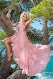 Beautiful blonde sexy shapely female model in a pink ballroom amazing carnival evening gown, wedding lies on the old tree Royalty Free Stock Photography