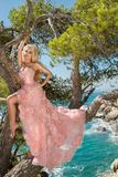 Beautiful blonde sexy shapely female model in a pink ballroom amazing carnival evening gown, wedding lies on the old tree Stock Photo