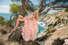Beautiful blonde sexy shapely female model in a pink ballroom amazing carnival evening gown, wedding lies on the old tree. In the background you can see rough Royalty Free Stock Photo