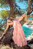 Beautiful blonde sexy shapely female model in a pink ballroom amazing carnival evening gown, wedding lies on the old tree. In the background you can see rough Stock Photography