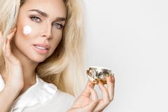 Beautiful blonde woman model holding a cream in her hand and creaming. Her face stock photo