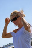 Beautiful blonde in shades. Attractive blonde woman at the beach is fixing her hair or adjusting her sunglasses wearing a shiny clingy tee shirt Stock Image