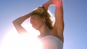 Beautiful blonde shaking her hair on sunny day stock video footage