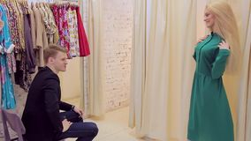 Beautiful blonde showing green dress to her boyfriend in women`s clothing store stock footage