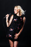 Beautiful blonde singing woman with microphone. Stock Photos