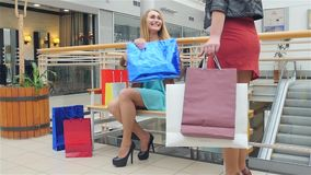 Beautiful blonde sitting on a bench Mall. Slow. Two beautiful girlfriends found on a bench in the store and begin to show who bought. Slow motion stock video footage