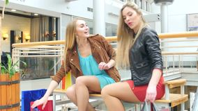 Beautiful blonde sitting on a bench Mall. Two beautiful girlfriends found on a bench in the store and begin to show who bought stock video