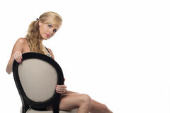 Beautiful blonde sitting in a chair royalty free stock photo