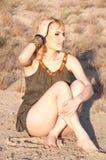 Beautiful blonde sitting cross-legged on the sa Stock Photos