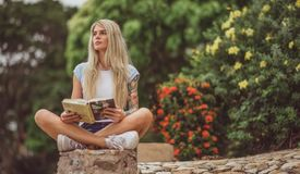 Beautiful blonde sitting in the flower garden and reading a book. Arms tattooed. modern, trendy student.  royalty free stock photo