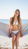 Beautiful blonde sitting on hammock and smiling Royalty Free Stock Photos