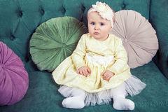Beautiful blonde small girl with yellow dress and flower on her head Stock Images