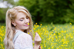 Beautiful blonde is smelling flowers stock photography