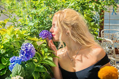 Beautiful blonde is smelling hydrangeas. concept of beauty  na Stock Photography