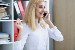 Beautiful blonde smiling businesswoman talk cellphone. In office portrait. Stay in touch best cellular price A woman is informed that she won a prize in the Royalty Free Stock Photography